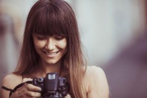 Smiling woman holding camera