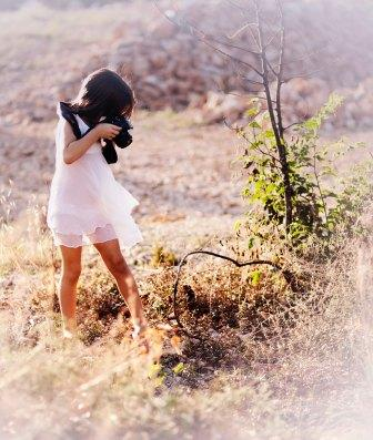 women in the nature holding her camera, making a picture