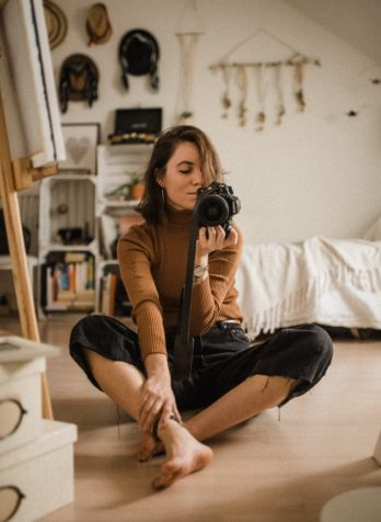 women setting in her bedroom holding her camera