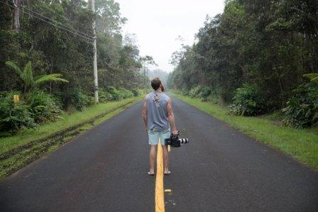 man holding camera on a road